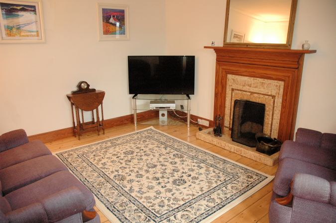 Tigharry Cottage, Lochcarron, has a comfortable and homely living room with an open fire.