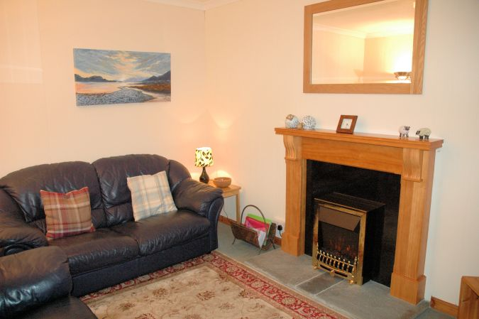 Bruaich Cottage, Lochcarron, has a cosy and homely living room with a traditional fireplace.