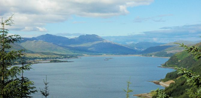 "The view looking along the length of Loch Carron with its namesake, the village of Lochcarron, stretching along the north shoreand the unmistakable shape of Fuar Tholl, known locally as ""wellington"", in the centre background."