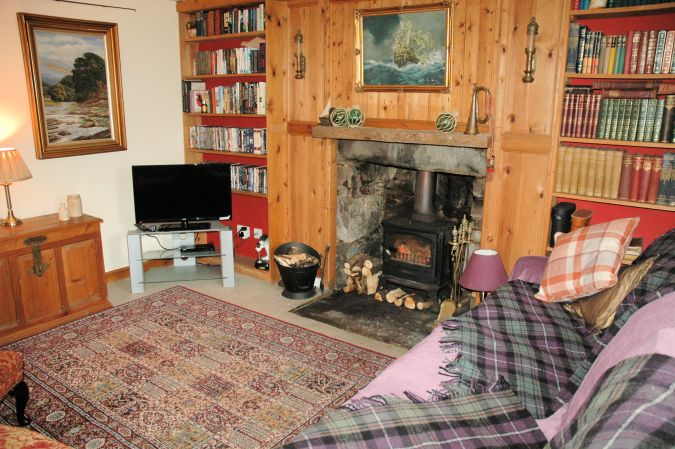 Roseate Cottage, Lochcarron, has a cosy and homely living room with a log burning stove.